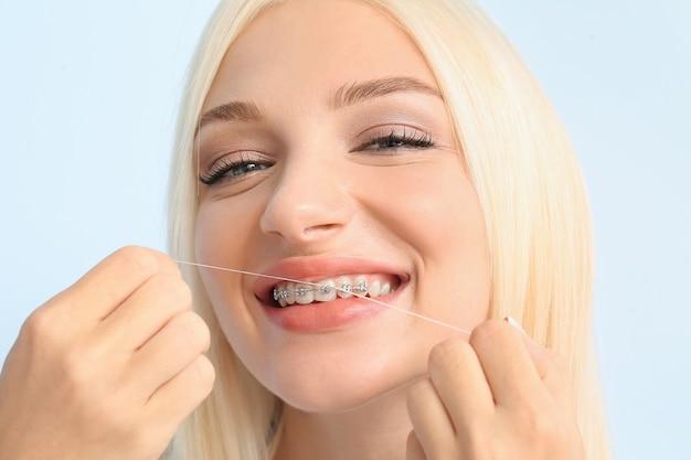 Jovem mulher com aparelho dentário e fio dental na cor de fundo