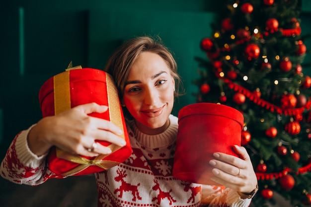 Jovem mulher com árvore de natal segurando caixas vermelhas