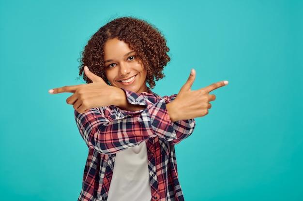 Jovem mulher com as mãos cruzadas, parede azul, emoção positiva. expressão facial, pessoa do sexo feminino olhando para a câmera no estúdio, conceito emocional, sentimentos