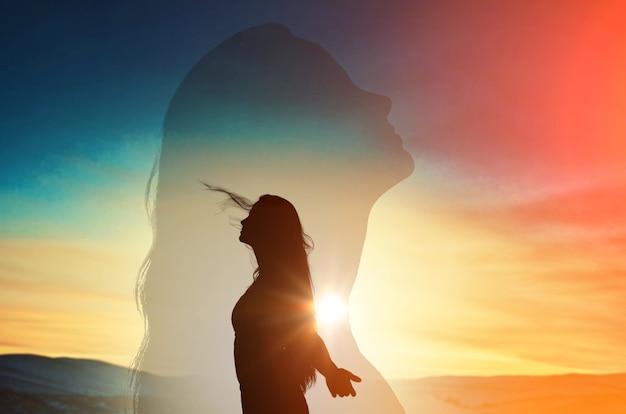 Jovem mulher com as mãos levantadas no fundo do céu do sol.