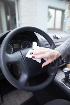 Jovem mulher com as mãos limpando a poeira do carro com um pano