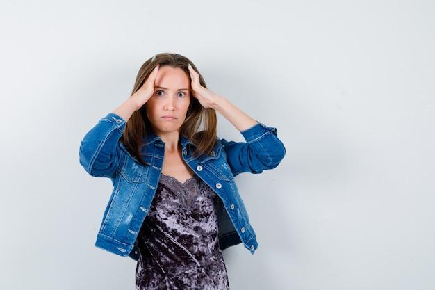 Jovem mulher com as mãos na cabeça em jaqueta jeans e olhando confusa, vista frontal.