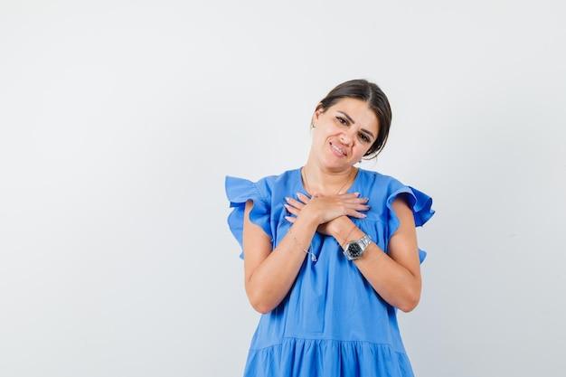 Jovem mulher com as mãos no peito com um vestido azul e parecendo envergonhada