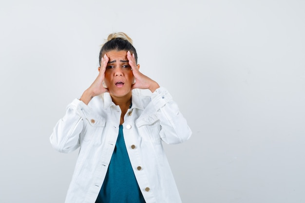 Jovem mulher com as mãos no rosto na jaqueta jeans branca e olhando chateada, vista frontal.