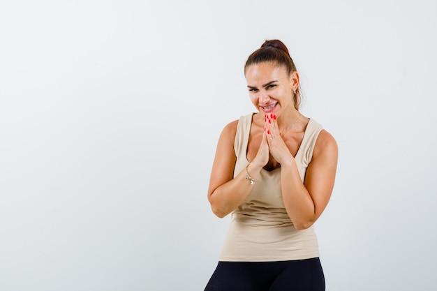 Jovem mulher com as mãos postas em súplica, usando um top bege e parecendo em paz