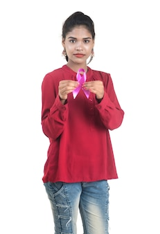 Jovem mulher com as mãos segurando uma fita rosa de conscientização do câncer de mama