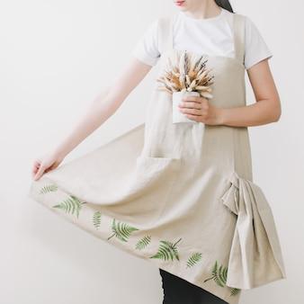 Jovem mulher com avental de linho. têxteis de cozinha. tecido de linho