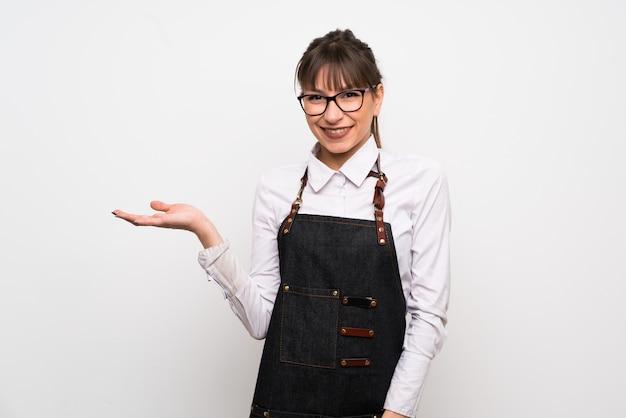 Jovem mulher com avental segurando copyspace imaginário na palma da mão para inserir um anúncio