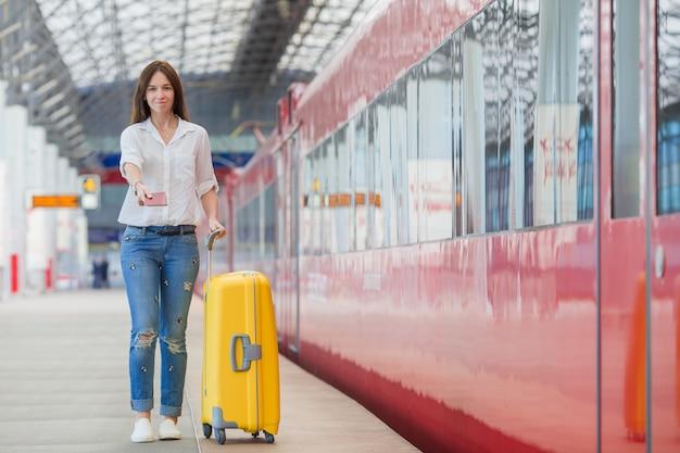 Jovem mulher com bagagem em uma estação de trem. turista caucasiana, esperando seu trem expresso