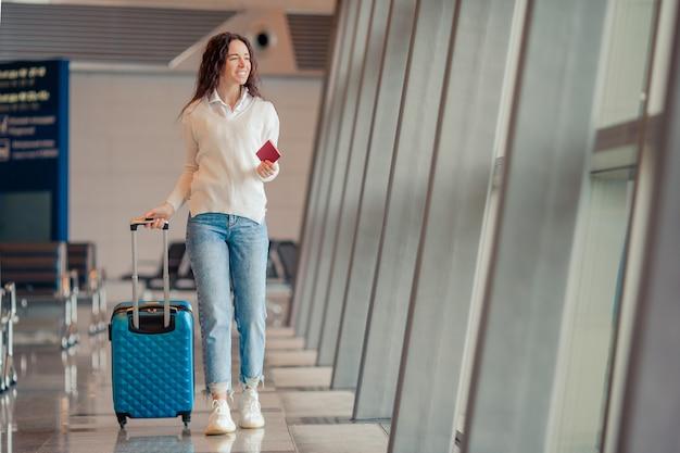 Jovem mulher com bagagem no aeroporto internacional. passageiros de avião em um saguão do aeroporto esperando o avião do voo