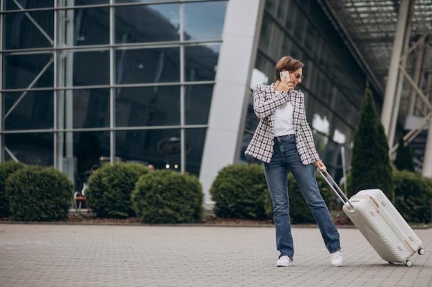 Jovem mulher com bagagem no aeroporto, viajando e falando ao telefone