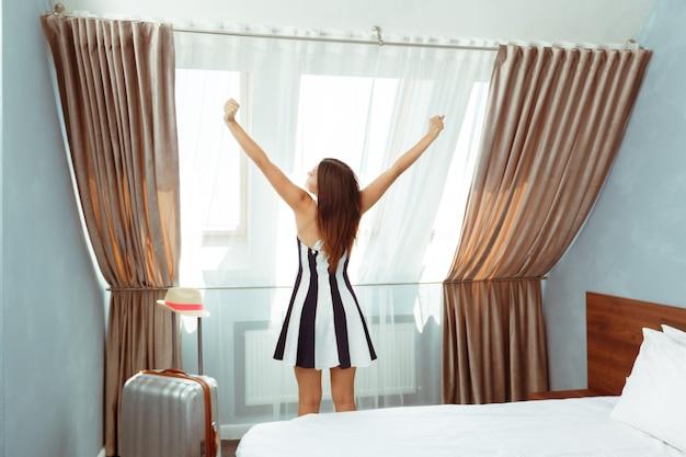 Jovem mulher com bagagem no quarto de hotel