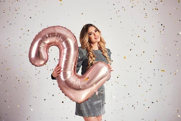 Jovem mulher com balões em formato duplo