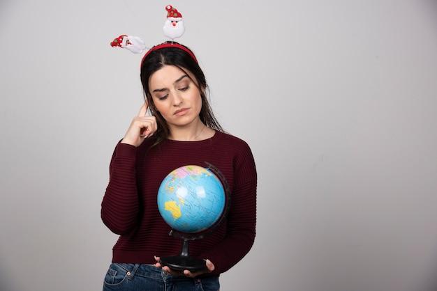Jovem mulher com bandana de natal, olhando para um globo terrestre.