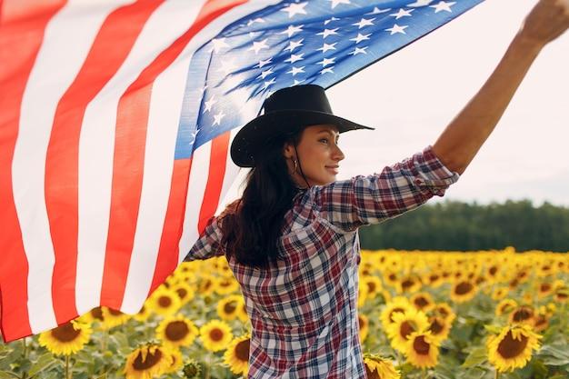 Jovem mulher com bandeira americana no campo de girassol colheita conceito dos eua