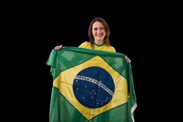 Jovem mulher com bandeira brasileira em uma parede preta.