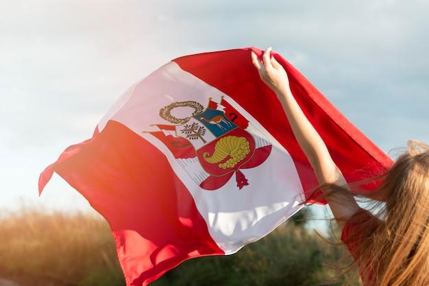 Jovem mulher com bandeira do peru ao ar livre