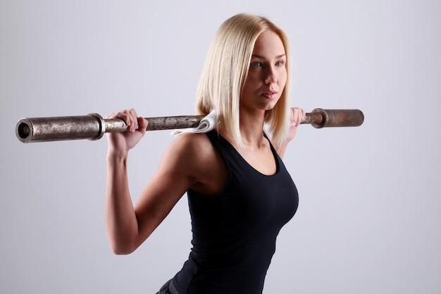 Jovem mulher com barra de exercício