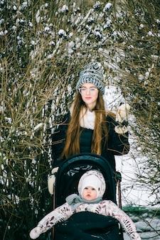 Jovem mulher com bebê no carrinho no mato em dia de inverno