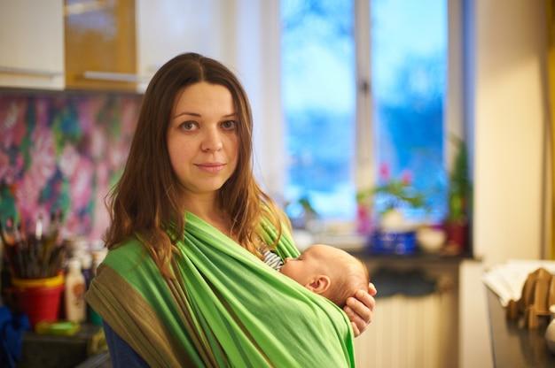 Jovem mulher com bebê recém-nascido na tipóia com um fundo desfocado em casa