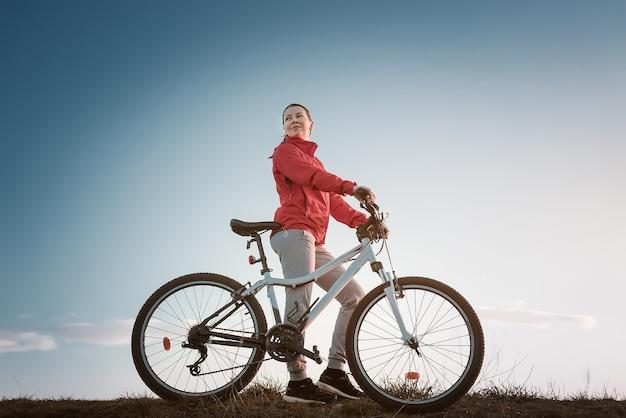 Jovem mulher com bicicleta de montanha ao pôr do sol.
