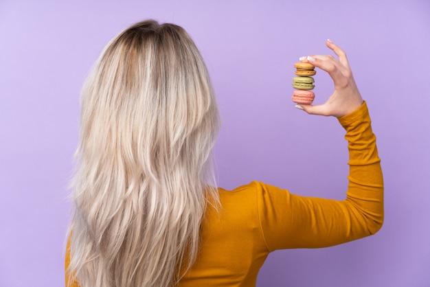 Jovem mulher com biscoitos sobre parede isolada