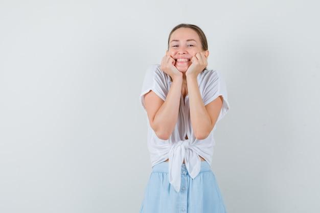 Jovem mulher com blusa, saia apoiando o rosto nas mãos e parecendo uma fofa