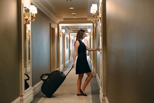 Jovem mulher com bolsa e mala em um elegante terno caminha o corredor do hotel para o quarto dela.