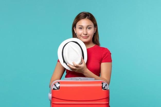 Jovem mulher com bolsa vermelha segurando o chapéu no espaço azul