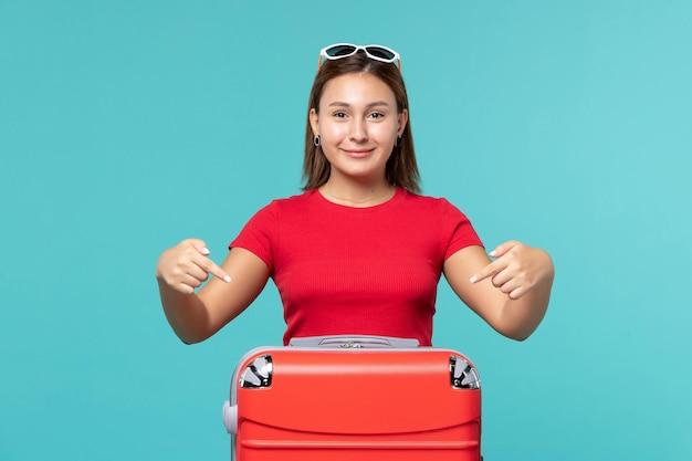 Jovem mulher com bolsa vermelha sorrindo no espaço azul de frente