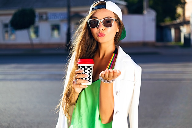 Jovem mulher com boné e óculos de sol bebendo café jogando um beijo na rua