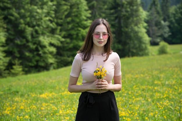 Jovem mulher com buquê de flores silvestres em um gramado ensolarado.