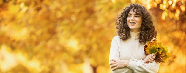 Jovem mulher com buquê de outono de folhas de plátano. menina com aparelho dentário e cabelo encaracolado.
