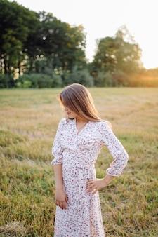 Jovem mulher com cabelo bonito, posando em campo ao pôr do sol. moda, independência