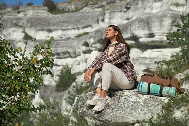 Jovem mulher com cabelo castanho relaxando na rocha, mantendo os olhos fechados e aproveitando o passatempo favorito ao ar livre.