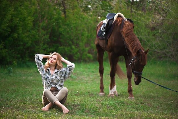 Jovem mulher com cabelo comprido, posando com um cavalo castanho em uma floresta em um prado ensolarado.