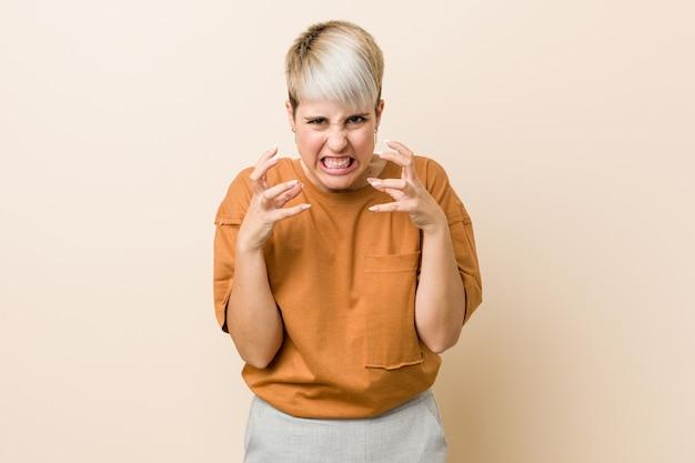 Jovem mulher com cabelo curto chateado, gritando com as mãos tensas
