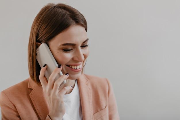 Jovem mulher com cabelo curto em uma jaqueta brilhante sorri e fala por telefone em branco.