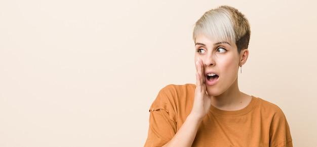 Jovem mulher com cabelo curto está dizendo uma notícia secreta sobre frenagem quente e olhando de lado