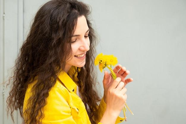 Jovem mulher com cabelo encaracolado com flores nas mãos.