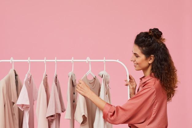 Jovem mulher com cabelo encaracolado escolhendo as roupas que estão penduradas no cabide