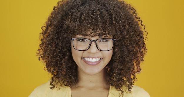 Jovem mulher com cabelo encaracolado, feliz com os óculos. conceito de cuidados com os olhos.