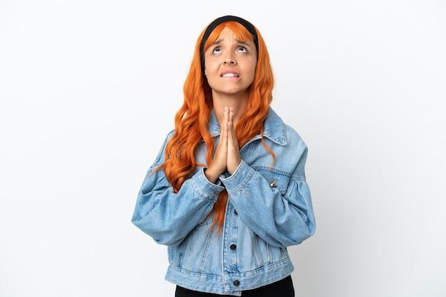 Jovem mulher com cabelo laranja, isolado no fundo branco mantém as palmas das mãos juntas. pessoa pede algo