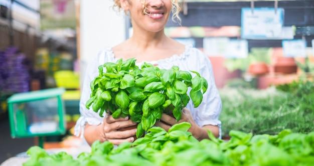 Jovem mulher com cabelo loiro encaracolado escolhe uma muda de manjericão em uma loja. conceito de cuidado e paixão pela natureza