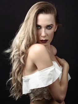 Jovem mulher com cabelo longo e olhos azuis contra o fundo preto com composição roxa.