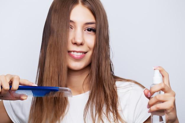 Jovem mulher com cabelo luxuoso aplica condicionador para cuidados com os cabelos