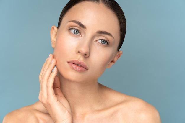 Jovem mulher com cabelo penteado com maquiagem natural, tocando a pele pura bem cuidada no rosto, cuidados de beleza
