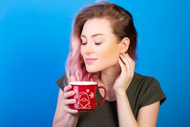 Jovem mulher com cabelo rosa, desfrutando de sua xícara de chá