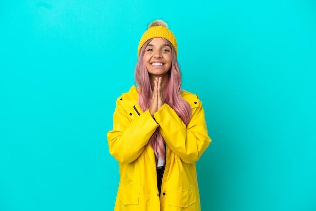 Jovem mulher com cabelo rosa, vestindo um casaco à prova de chuva, isolado em um fundo azul mantém as palmas das mãos juntas. pessoa pede algo