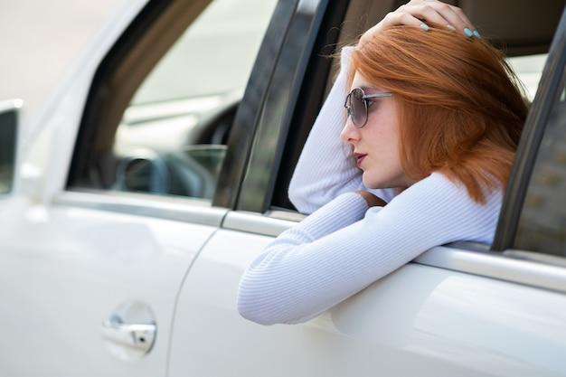 Jovem mulher com cabelo vermelho e óculos de sol, viajando de carro. passageiro olhando pela janela traseira de um táxi em uma cidade.